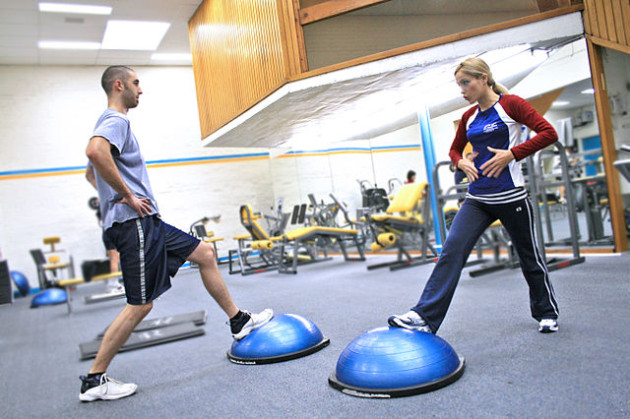 640px-Personal_trainer_showing_a_client_how_to_exercise_the_right_way_and_educating_them_along_the_way